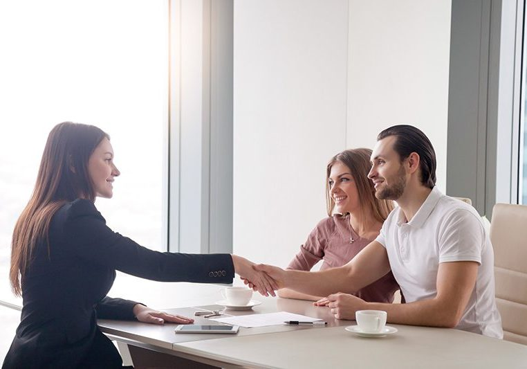Young prosperous couple meeting with female broker in real estate agency. Man and real estate agent shaking hands, happy to make a deal of buying property, investment advisor congratulating clients